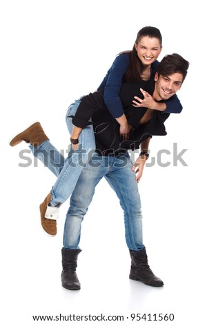 Happy young couple of a handsome man and beautiful woman. Girl is jumping in guy's back. Isolated on white background. High resolution studio image