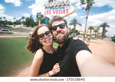 Happy young couple of tourists take selfie near Las Vegas Welcome sign. Two exited students take self portrait with a professional camera with Las Vegas billboard on the background, Nevada, USA - stock photo