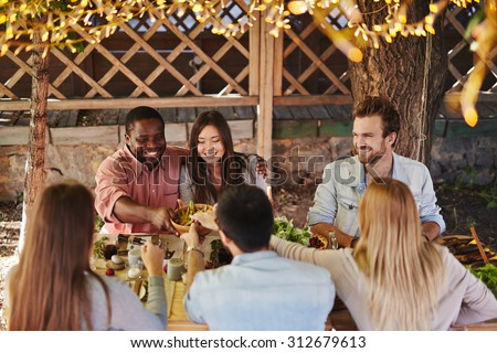 Happy young couple offering their friends traditional food by Thanksgiving table