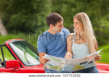 Happy young couple on a sunny day reading map