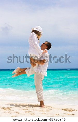 Happy young couple on a tropical beach - stock photo