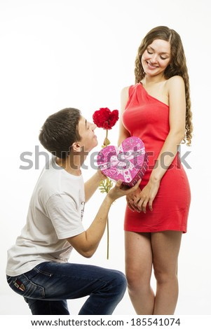 Happy young couple on a white background. Happy man giving a gift to his girlfriend
