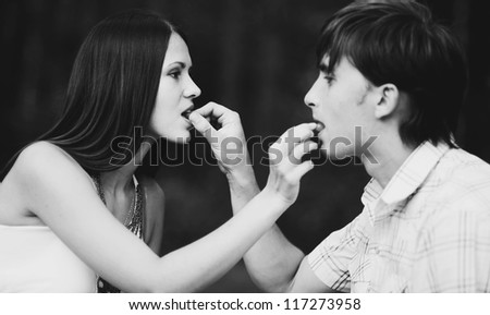Happy young couple on picnic feed each other grapes - stock photo
