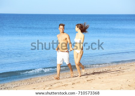 Happy young couple on sea beach at resort