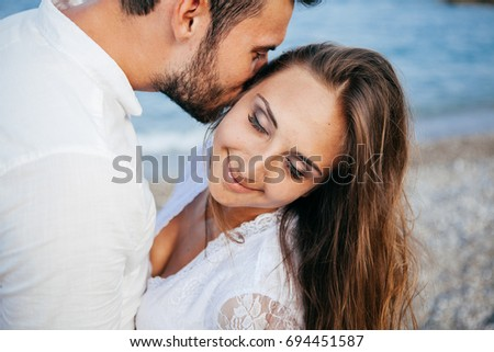 Happy young couple on the beach in love embracing and hugging smiling