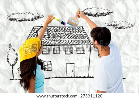 Happy young couple painting together against crumpled white page - stock photo