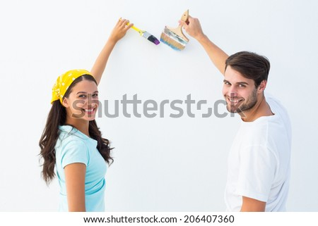 Happy young couple painting together on white background - stock photo