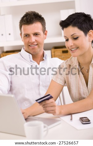 Happy young couple paying with credit card at home. - stock photo