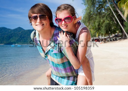 happy young couple playing around on tropical beach