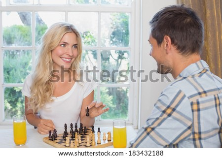 Happy young couple playing chess while having orange juice in the living room at home - stock photo