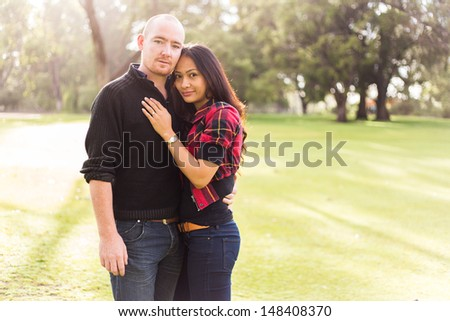 Happy young couple portrait, asian woman, caucasian man, hugging tenderly in a nice park  - stock photo