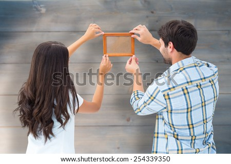 Happy young couple putting up picture frame against bleached wooden planks background - stock photo
