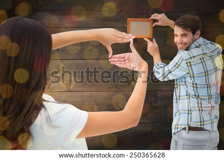 Happy young couple putting up picture frame against close up of christmas lights - stock photo