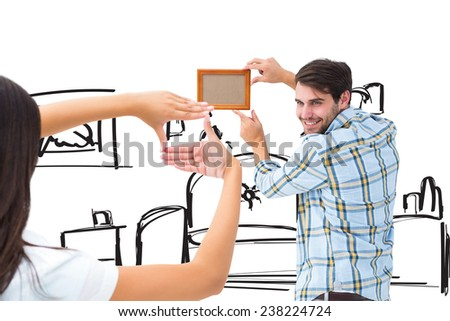 Happy young couple putting up picture frame against living room sketch - stock photo