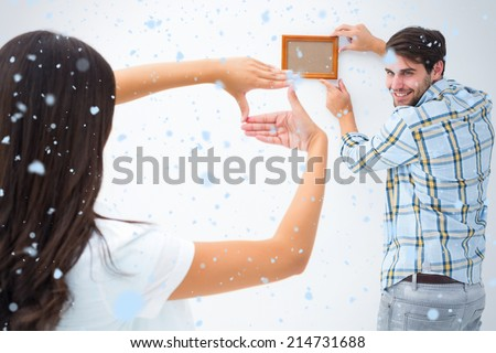 Happy young couple putting up picture frame against snow falling - stock photo