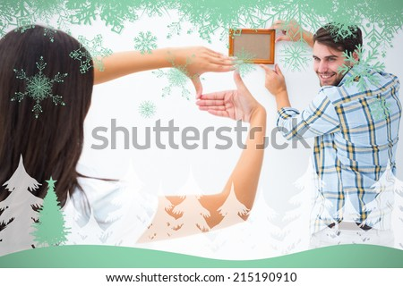 Happy young couple putting up picture frame against snowflakes and fir tree in green - stock photo