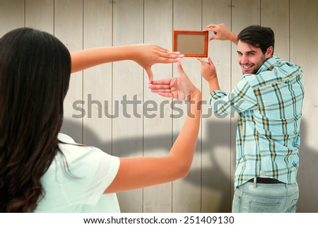 Happy young couple putting up picture frame against wooden planks - stock photo