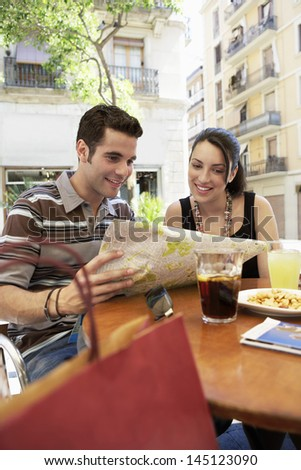 Happy young couple reading map together at sidewalk cafe - stock photo
