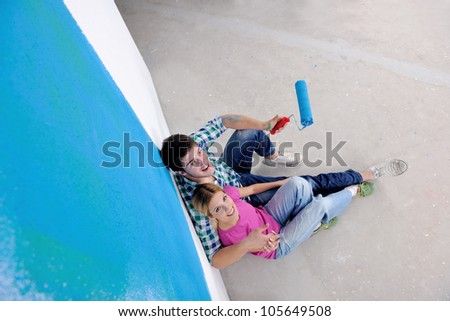 happy young couple relax after painting white wall in green and blue color in their new home
