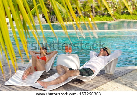 happy young couple relax and take fresh drink at summer vacation on swimmin pool