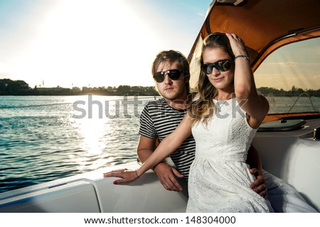 Happy young couple relaxing on a yacht - stock photo