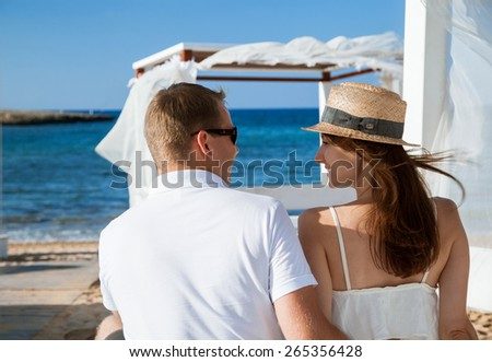 Happy young couple resting near the sea and  looking each other - stock photo