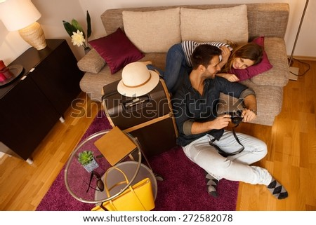 Happy young couple reviewing photos of holiday before leaving apartment. Above view. - stock photo