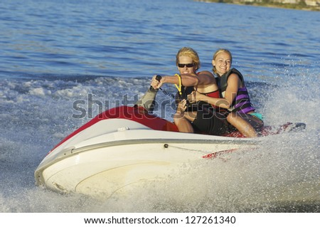 Happy young couple riding jet ski on lake - stock photo