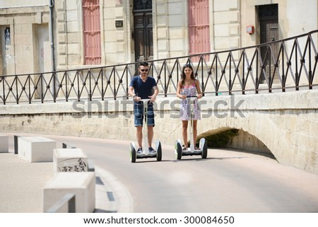 Happy young couple riding segway gyropode electric two wheels vehicle on a sightseeing tour - stock photo