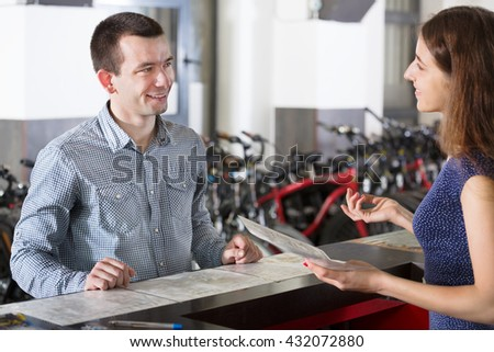 Happy young couple selecting bikes in the rental agency indoors. Focus on man