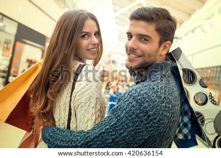Happy young couple shopping and holding bags. - stock photo