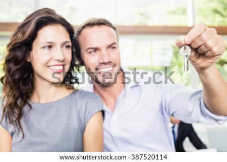 Happy young couple showing keys of their new house