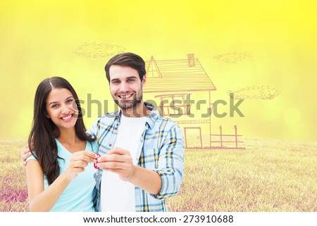 Happy young couple showing new house key against field against glowing lights - stock photo
