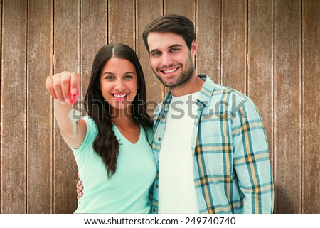 Happy young couple showing new house key against wooden planks - stock photo