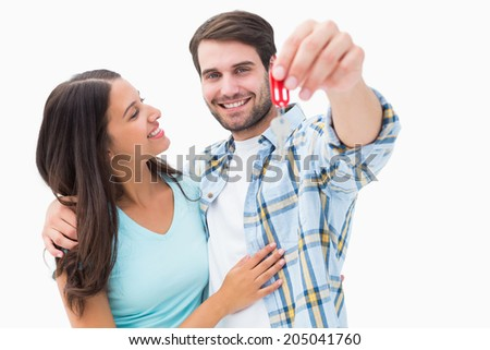 Happy young couple showing new house key on white background - stock photo