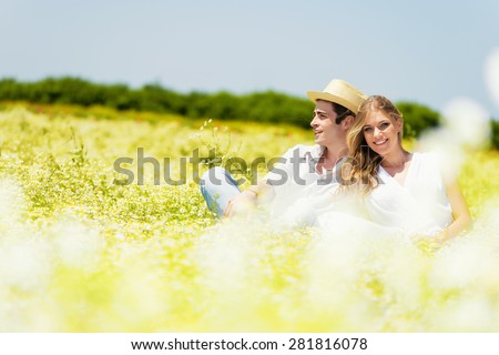 Happy, young couple sitting and enjoying in a chamomile, daisy meadow.Copy space - stock photo
