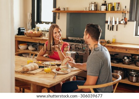 Happy young couple sitting at breakfast table in morning having a conversation. Young woman talking with her boyfriend while eating breakfast together in kitchen.