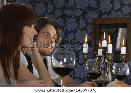 Happy young couple sitting at dining table - stock photo