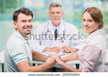Happy young couple sitting at doctor's office and smile. - stock photo