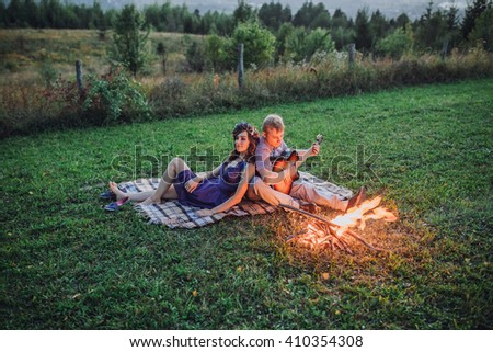 Happy young couple sitting by bonfire with guitar