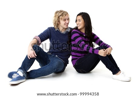happy young couple sitting down and looking at one another