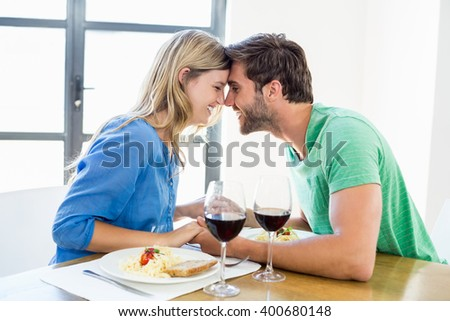 Happy young couple sitting face to face at dinning table - stock photo
