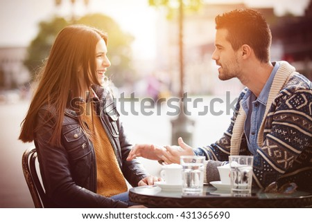 Happy young couple sitting in a cafe outside on a beautiful autumn day.