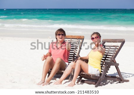 happy young couple sitting in beach chairs on tropical beach - stock photo