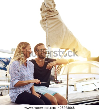 Happy Young Couple Sitting In front of a Sail Boat and Looking Into the Distance During Sunset Time. - stock photo