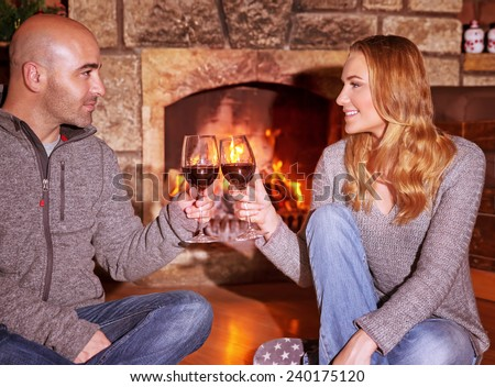 Happy young couple sitting near fireplace and drinking wine, enjoying romantic date, celebrating Valentines day in luxury cozy winter resort  - stock photo