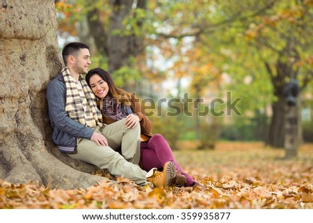 Happy young couple sitting next to the tree in a park