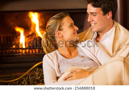 happy young couple sitting on couch in front of fireplace at home - stock photo