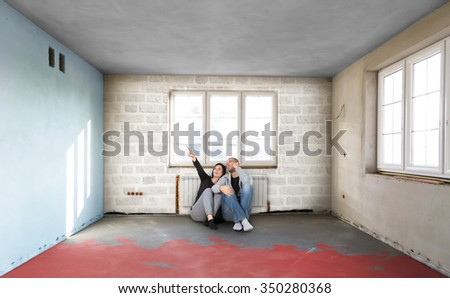 Happy Young Couple Sitting On Floor Looking Up While Dreaming Their New Home. Building in a developer - stock photo