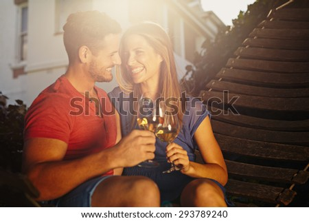 Happy young couple sitting on hammock toasting wine and looking at each other smiling. Loving young couple relaxing with a glass of wine in backyard on a bright sunny day. - stock photo